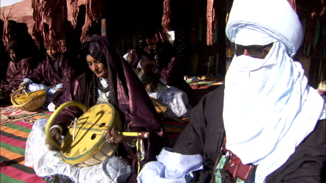 Tuareg musicians play traditional instruments under canopies in the desert. Available in HD.
