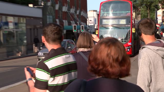 commuters queuing for buses and rmt picket line england london ealing broadway paddington at end ext rmt picket with flag / police officer helping... - ealing stock videos and b-roll footage