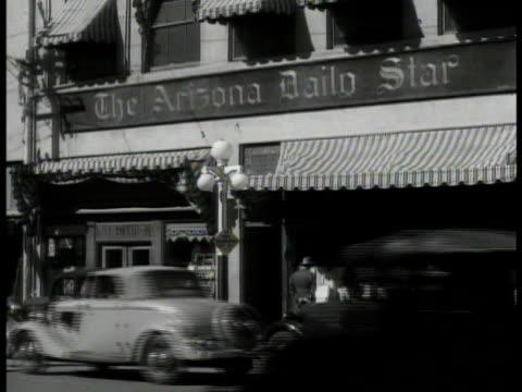 vídeos y material grabado en eventos de stock de tucson landscape, cactuses. arizona daily star' shop, traffic fg. int editor william r. matthews typing at desk. vs newspaper '...taxpayers aid...;... - 1935