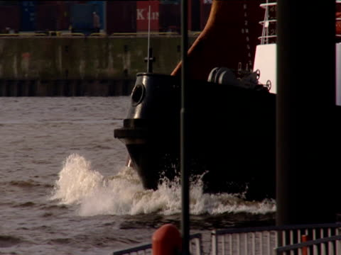 tug boat accompanies large tanker along river elbe as it leaves port tilt up over tanker to hook of container terminal crane hamburg - tug boat stock videos & royalty-free footage