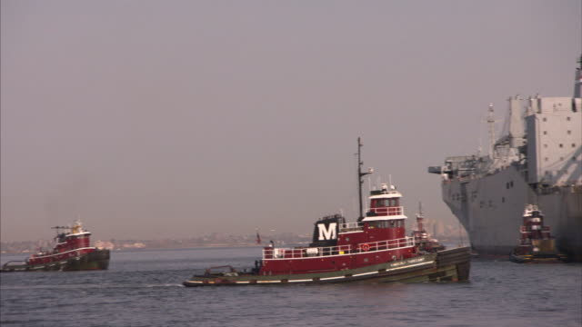 A tug boat cruises behind a larger vessel in the ocean.