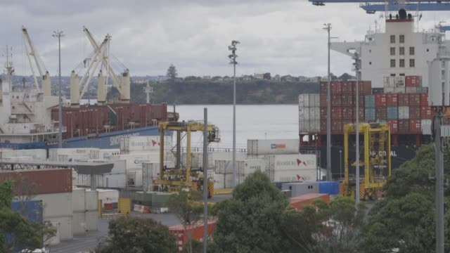 A tug boat guides a ship in the harbour near a Ports of Auckland terminal in Auckland New Zealand on Friday Dec 9 Straddle carriers manufactured by...