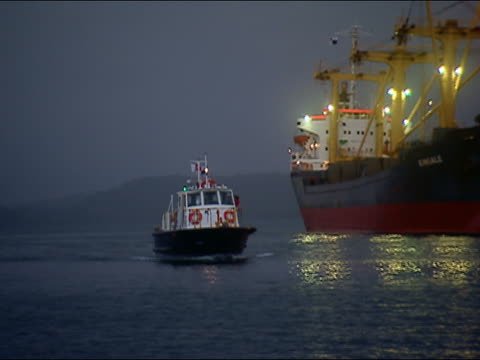vidéos et rushes de zo, ms tug boat passing large industrial ship at night, panama canal - remorqueur