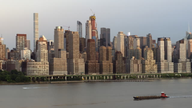 A tug boat pushes a barge up the Hudson River.  The Manhattan Skyline is behind.