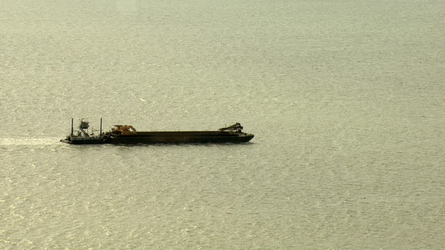 vidéos et rushes de a tug boat pushes a larger container ship through calm waters. - remorqueur