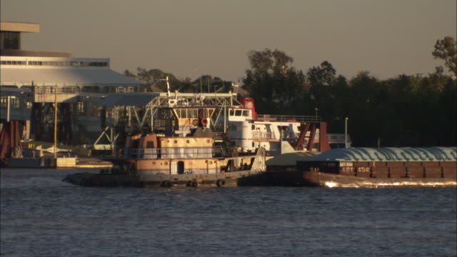 A tug boat pushes two containers along the Mississippi river. Available in HD