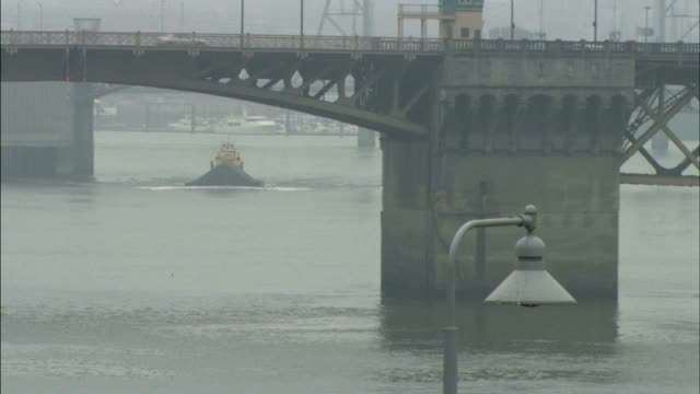 LS Tug boat pushing something down Willamette River w/ bridge FG ZO HA WS Burnside Bridge traffic w/ heavy fog BG