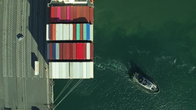 tug boat sailing away from newly arrived container ship in port of long beach - aerial - tug boat stock videos & royalty-free footage