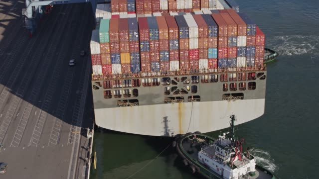 tug boats manoeuvering massive cargo ship against dock - aerial shot - mercanzia video stock e b–roll
