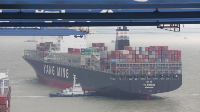 a tug pushes a container ship out to sea at the at the guangzhou nansha container port in guangzhou china on monday feb 1 2016 shipping containers... - benjamin franklin stock videos & royalty-free footage