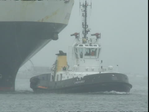 Tug towing APL Pearl Container ship, misty, rainy weather, Container Terminal, Southampton, UK