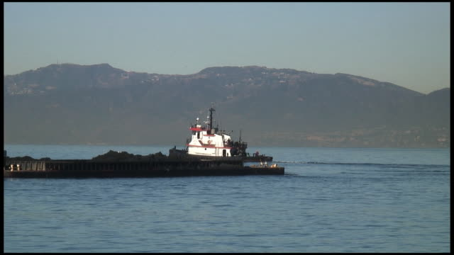 (hd1080i) tug tows barge: part 1 of 2 - towing stock videos and b-roll footage