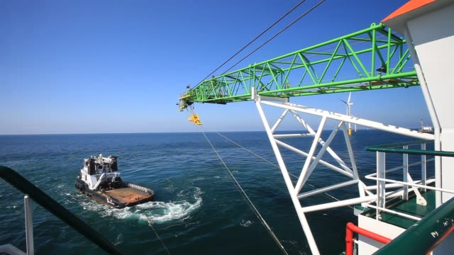 a tug tows the jack up barge krakken constructing the walney offshore windfarm off cumbria uk - health and safety stock videos & royalty-free footage