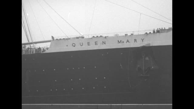MS tugboat alongside RMS Queen Mary / pan starboard side of Queen Mary with name on it / tugboat pulls into port / LS Winston Churchill disembarking...