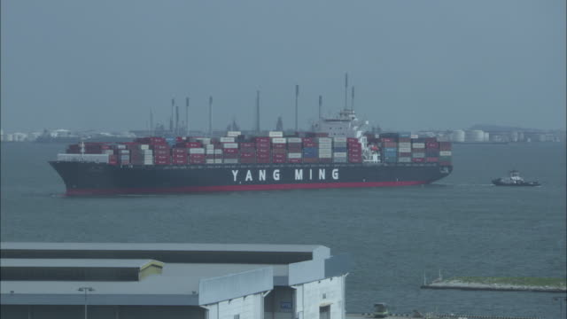 A tugboat approaches the container ship, Yang Ming.