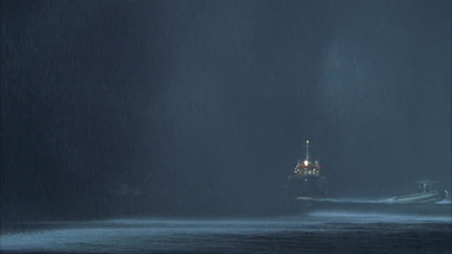 vidéos et rushes de ws pan tugboat at sea in heavy rain at night - remorqueur