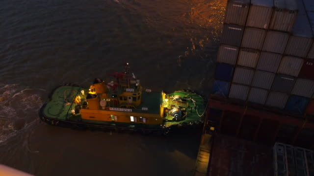 A tug-boat helps berth a large container ship at night into a port in Southern China