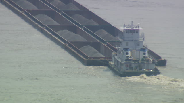 MS POV Tugboat moving coal filled barge in river / Memphis, Tennessee, United States
