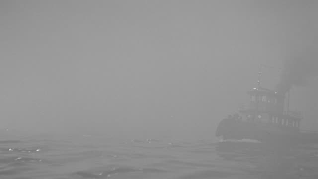ms tugboat passes in  ocean from fog  - tugboat stock videos and b-roll footage