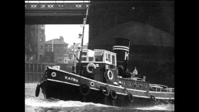 tugboat passes under tower bridge on river thames in london; 1967 - moving past stock videos & royalty-free footage