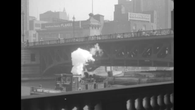 vídeos de stock, filmes e b-roll de tugboat pulling barge goes under bridge with a lot of traffic on it / vs ships and barges go through open drawbridge / drainage canal / four towered... - 1920 1929