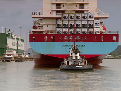 pan tugboat pulling cargo ship loaded with containers - tugboat stock videos and b-roll footage