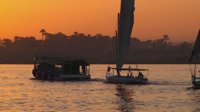 ms tugboat pulling row of sail boats through nile river at sunset / cairo, egypt - タグボート点の映像素材/bロール