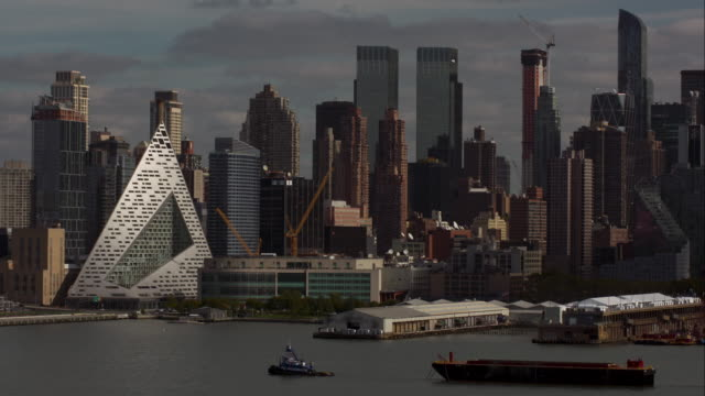 Tugboat pulls shipping container ship along Hudson River in front of New York City skyline