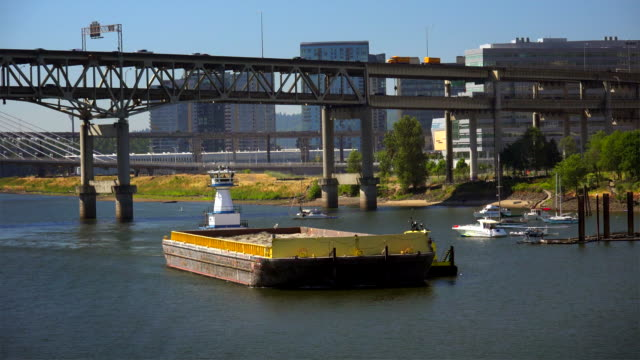 A tugboat pushes a barge of sand down the Willamette River in Portland, Oregon