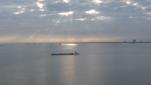 vidéos et rushes de a tugboat pushes a barge under a glowing sky. - golfe du mexique