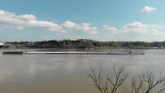 a tugboat pushes a barge up mississippi river in natchez mississippi - ミシシッピ川点の映像素材/bロール