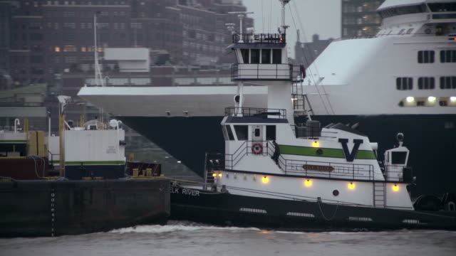 a tugboat pushes a barge up the hudson while it floats past a cruise ship.   - western script stock videos & royalty-free footage