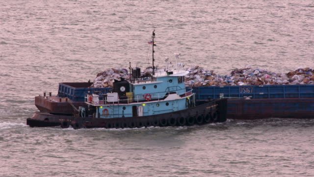 Tugboat pushes barge full of city garbage along the Hudson River.