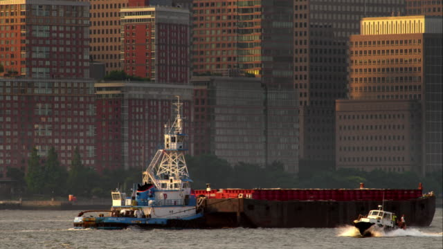 vidéos et rushes de tugboat pushes large barge along the hudson river in slow motion as a police boat speeds by during sunset. - remorqueur