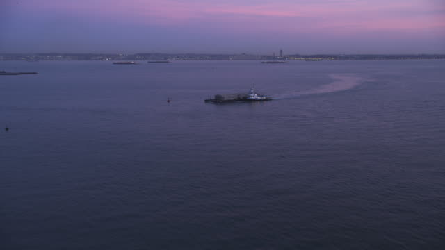 tugboat pushing a barge in upper bay at dusk, new york city in background. shot in 2011. - artbeats stock videos & royalty-free footage