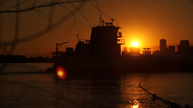 Tugboat pushing barge in silhouette across Mississippi River sun setting sun spots on lens bare tree branches FG city skyline BG Industry industrial...
