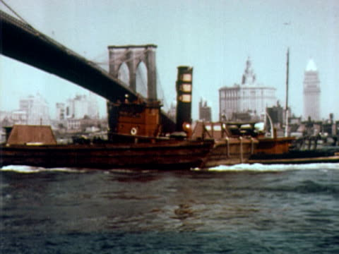 1960 WS tugboat pushing barge under the Brooklyn Bridge / skyline of lower Manhattan in background / New York City