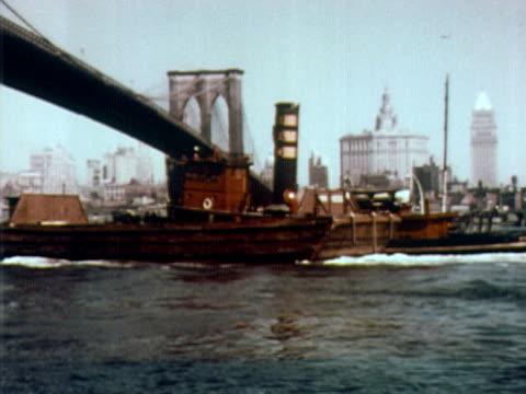 1960 ws tugboat pushing barge under the brooklyn bridge / skyline of lower manhattan in background / new york city - brooklyn bridge stock videos & royalty-free footage