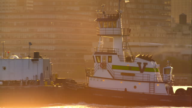 tugboat pushing barge up hudson river at dawn - tugboat stock videos and b-roll footage