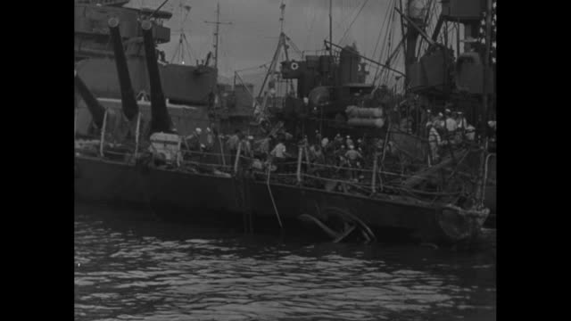 tugboat pushing battleship uss california / bottom up uss oklahoma / uss nevada / vs us flag flying on deck of uss west virginia with sailors heavy... - 真珠湾攻撃点の映像素材/bロール