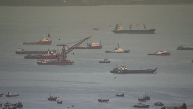 a tugboat sails away from a container crane in a crowded harbor. available in hd - harbour stock videos & royalty-free footage