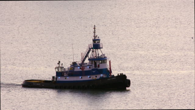 tugboat slowly moves along quiet and calm water that fills frame - tugboat stock videos and b-roll footage