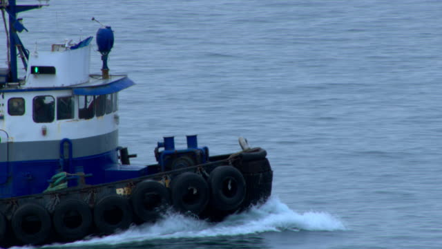 vidéos et rushes de a tugboat steams through a harbor. - remorqueur