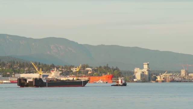 tugboat towing a big industrial ship in vancouver harbor, in front of the industrial zone and mountains.  panning camera motion, with the camera speed faster than ship. - tug boat stock videos & royalty-free footage