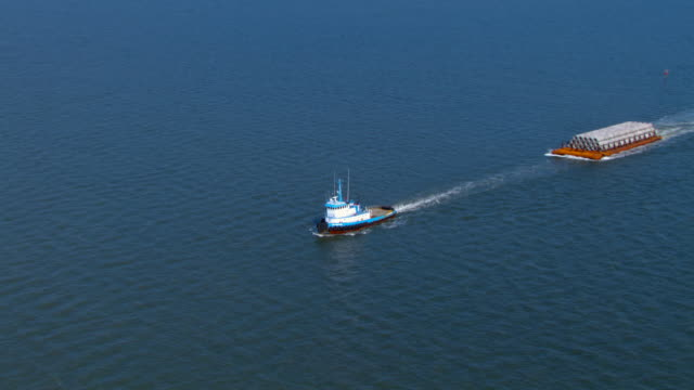 a tugboat tows a barge down the mississippi river. - tugboat stock videos and b-roll footage