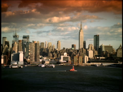 a tugboat travels near the skyline of midtown manhattan under a colorful sky. - tugboat stock videos and b-roll footage