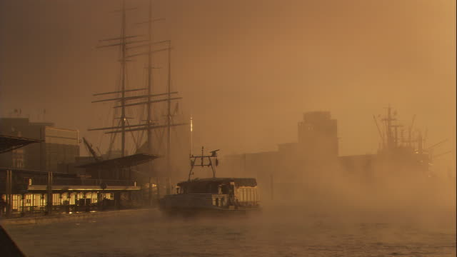 a tugboat travels through a foggy harbor. - tug boat stock videos & royalty-free footage