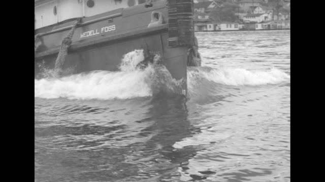 VS CU tugboat Wedell Foss bow through water / CU stern / CU Captain turns wheel / CU dial of engine order telegraph made by Chas Cory Son Inc / MS...