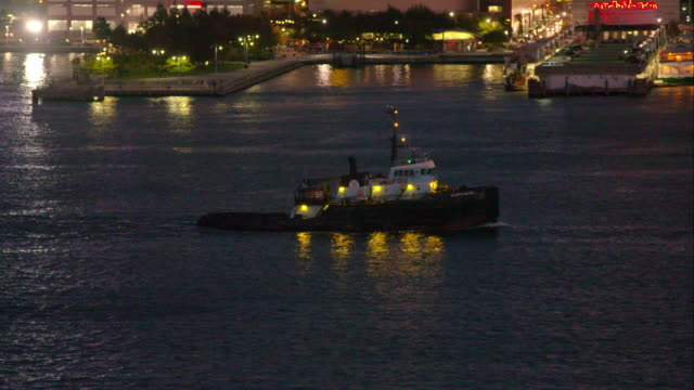 Tugboat with lights on moves along calm Hudson River at night in New York City