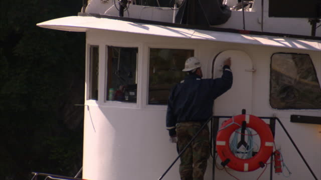 A tugboat worker enters a door into the cab of the boat.